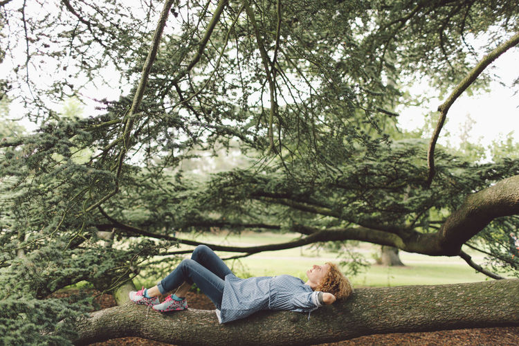 Woman lying on tree trunk at park