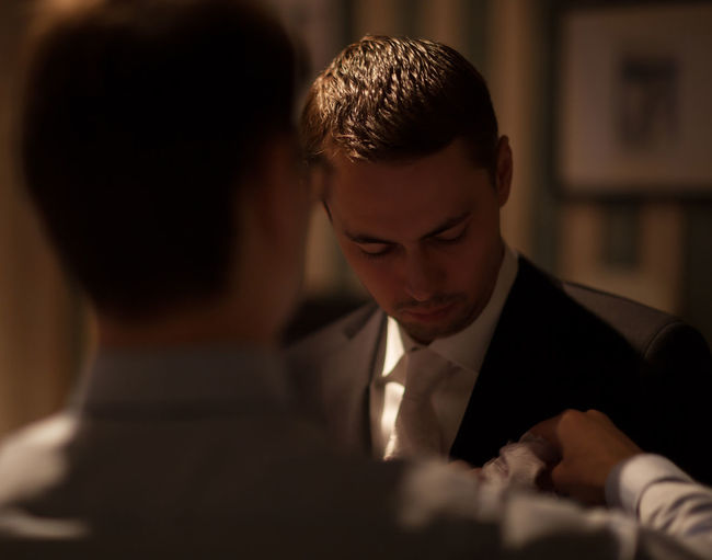 Rear view of groomsman adjusting napkin for bridegroom