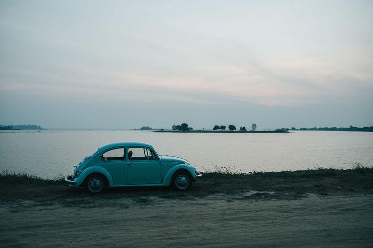 Vintage car on sea shore against sky