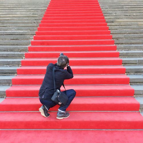 Rear view of a male paparazzi on red carpeted stairs