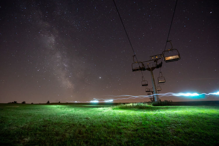 Chair lift on field against sky at night