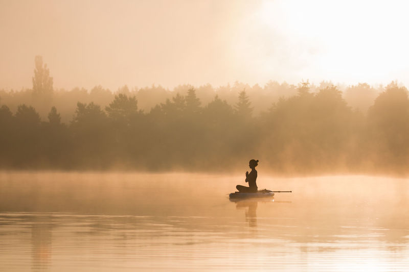 Silhouette woman meditating in lake against sky during sunrise