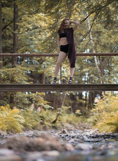 Portrait Of Young Woman Standing On Footbridge Against Trees In Forest