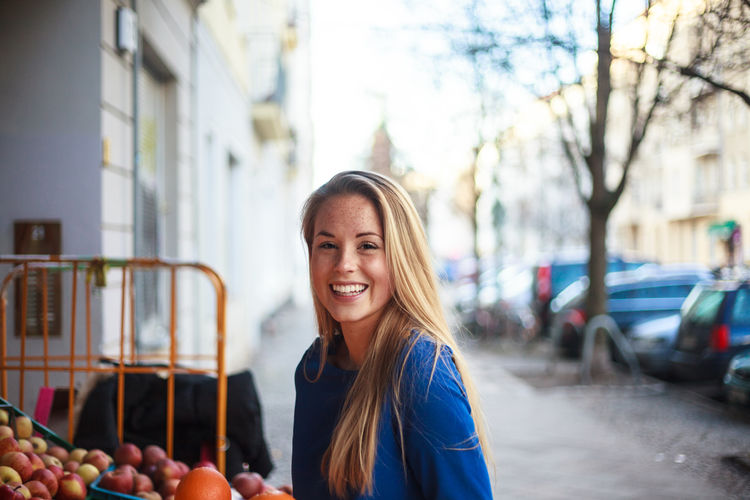 Girl choosing fruit at a Adult Adults Only Beautiful Woman Casual Clothing Cheerful City Day Focus On Foreground Happiness Long Hair Looking At Camera One Person One Woman Only One Young Woman Only Outdoors People Portrait Real People Smiling Young Adult Young Women