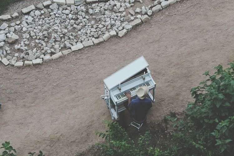 High Angle View Of Man Playing Piano Outdoors