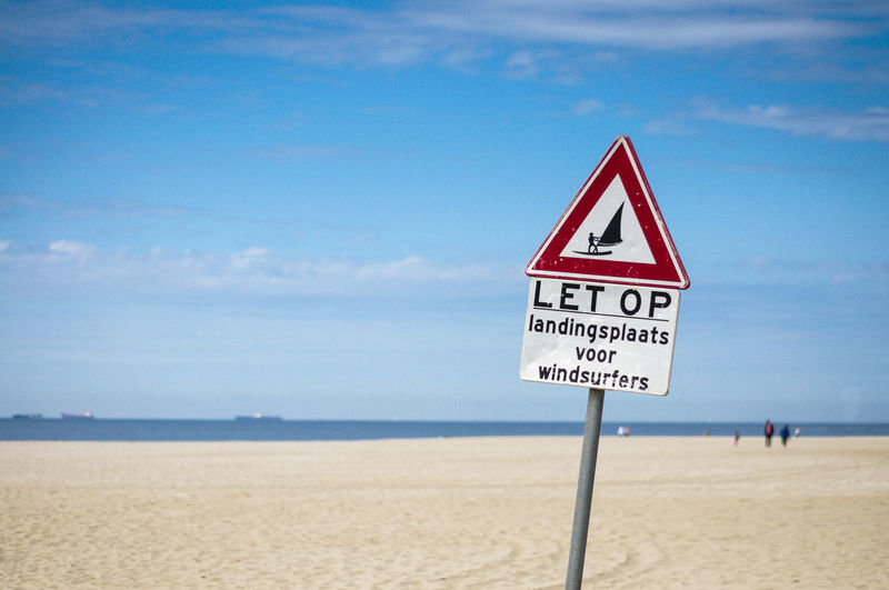 Curious information sign on beach against sky
