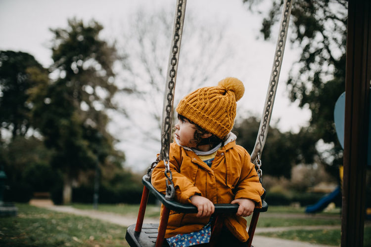 Low section of boy on swing in playground
