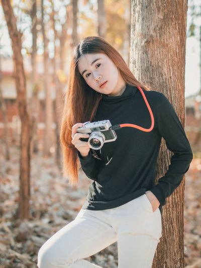 Portrait of woman with camera outdoors