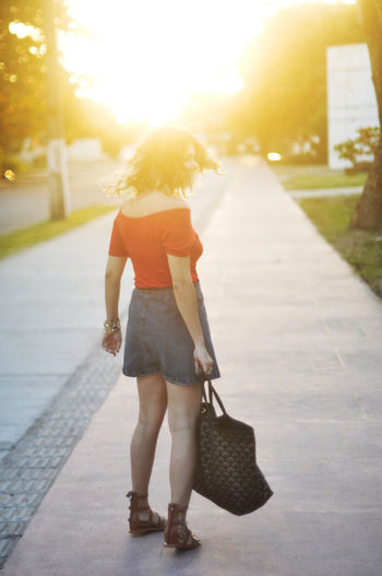 Rear View Of Woman Standing On Street In City During Sunset