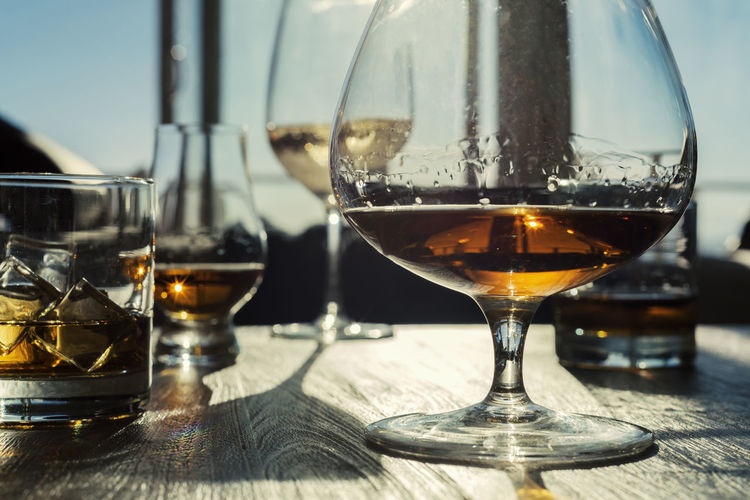 Low angle view of a variety of alcoholic drinks on wooden table. Amber Choice Entertaining Ice Liquor Old Fashioned Rustic Alcohol Bar Booze Brandy Cognac Crystal Dram Drink Masculine Neat Rocks Scotch Stemware Table Variety Wine Wooden