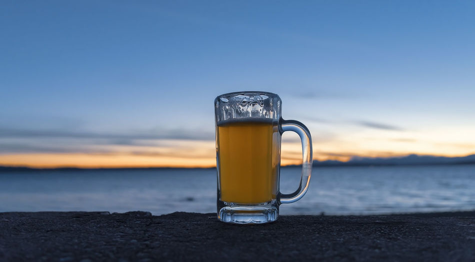 Beer in a mug at sunset, wide view.
