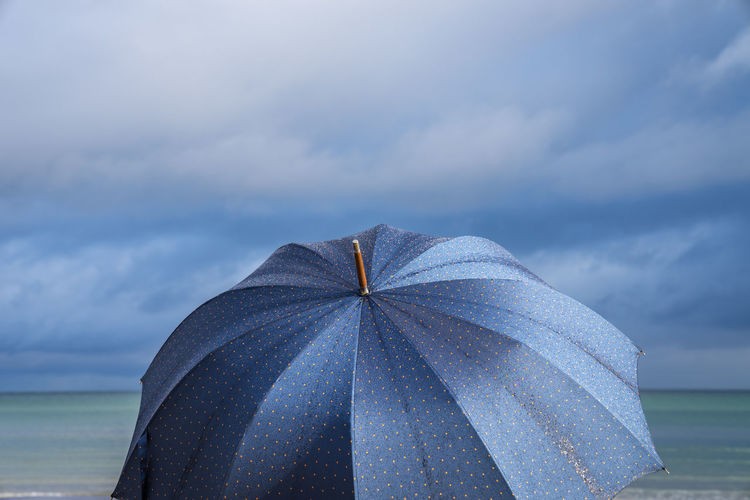 Close-up of open umbrella against cloudy sky at beach