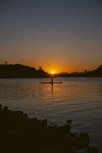 Silhouette person on lake against sky during sunset