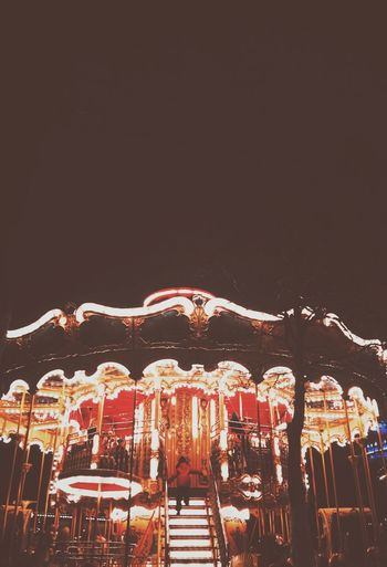 Low angle view of illuminated carousel against clear sky at night