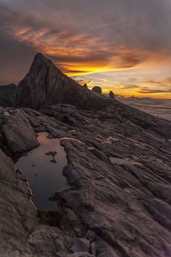 Rock formation by sea against orange sky