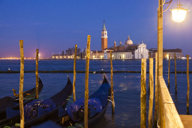 Gondolas moored on grand canal against church of san giorgio maggiore at dusk