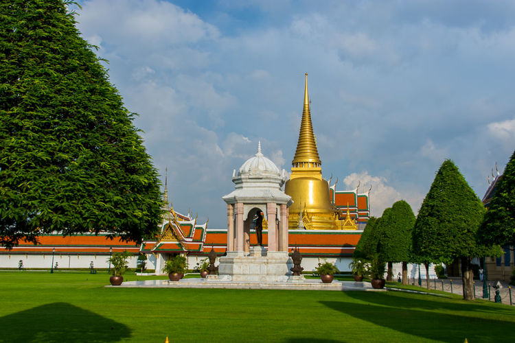 Wat Phra Kaeo Wat Phra Kaeo Architecture Belief Building Building Exterior Built Structure Cloud - Sky Grass Green Color Incidental People Nature Outdoors Place Of Worship Plant Religion Sky Spire  Spirituality Tourism Travel Travel Destinations Tree