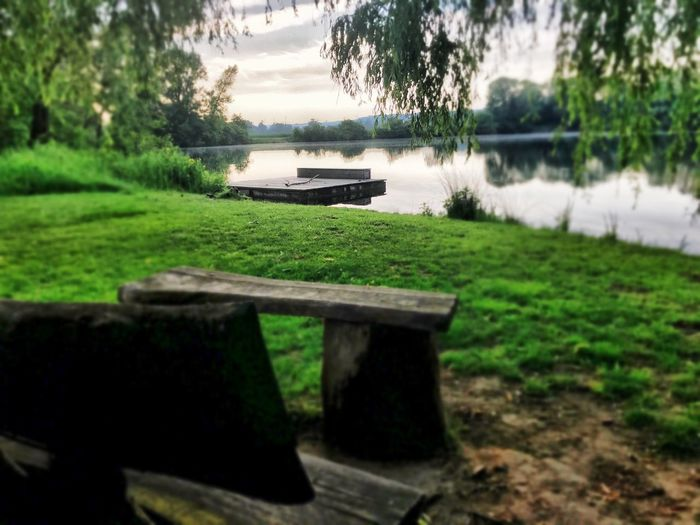 Bench by lake against sky