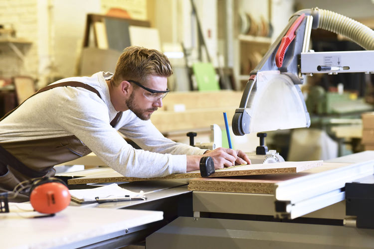 Side view of man working on table