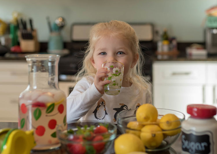 Portrait Of Cute Girl Drinking Juice In Kitchen At Home