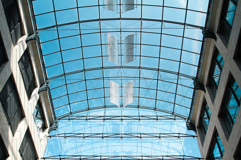 Low Angle View Of Glass Ceiling Against Blue Sky