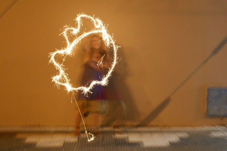 Blurred motion of woman holding illuminated sparkler against wall at night