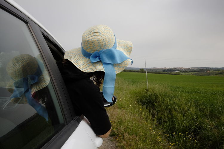 woman with hat looks out of the car window Mode Of Transportation Transportation Car Motor Vehicle Grass One Person Land Vehicle Day Land Plant Casual Clothing Field Lifestyles Nature Real People Rear View Adult Sky Environment Outdoors Hat Freedom
