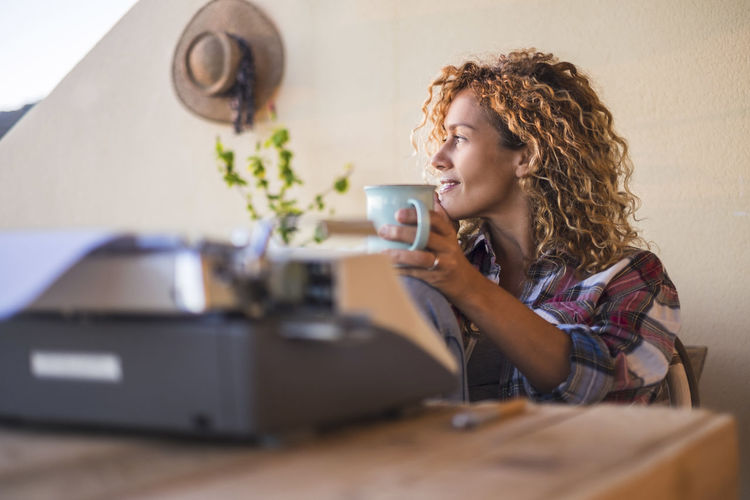 Woman holding coffee cup by typewriter sitting at home
