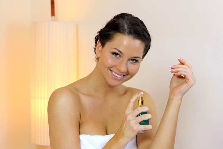 Woman applying perfume from a glass flacon Eau De Cologne Feminine  Vapor Woman Applying Beautiful Woman Beauty Close-up Cosmetics Fragant Girl Glass Flacon Happiness Holding Indoors  Looking At Camera One Person Perfume Perfume Sprayer Portrait Smelling Smiling Young Adult