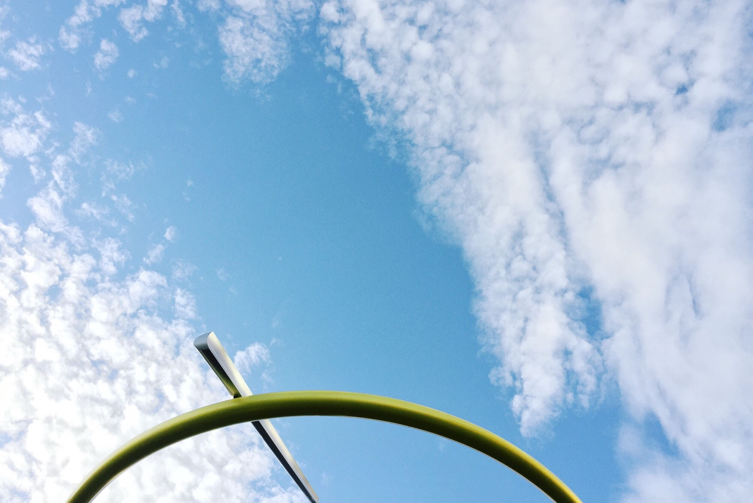 sky, low angle view, cloud - sky, blue, cloud, part of, nature, day, close-up, cropped, outdoors, cloudy, no people, metal, beauty in nature, street light, pole, yellow, tranquility, growth