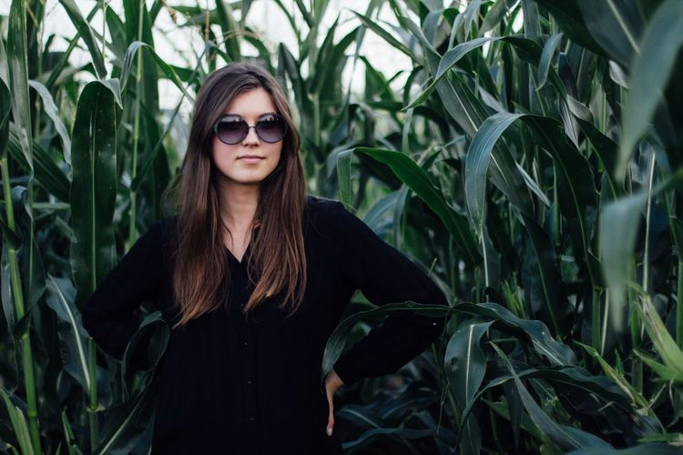 Young woman standing against crops on field