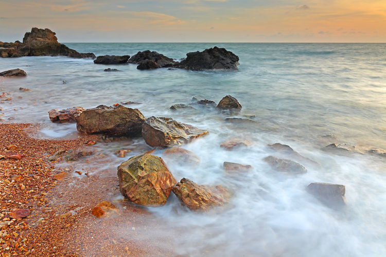 Beautiful sunset on the sea with rocks in foreground, In the eastern part of Thailand Sea Water Rock Rock - Object Beauty In Nature Solid Sky Scenics - Nature Beach Horizon Over Water Motion Land Horizon Sunset Rock Formation Nature Long Exposure Tranquility Cloud - Sky No People Outdoors Rocky Coastline Breaking Rayban Heavenly Weather Relaxing Dramatic Sky Dramatic Dramatic Landscape Nature Waves Coastline Coastline Landscape ASIA Asian  Travel Thailand