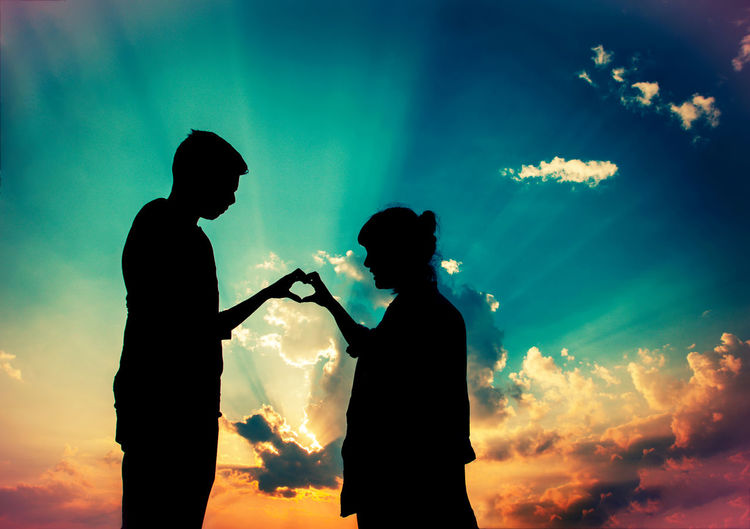 Low angle view of silhouette couple making heart shape against sky