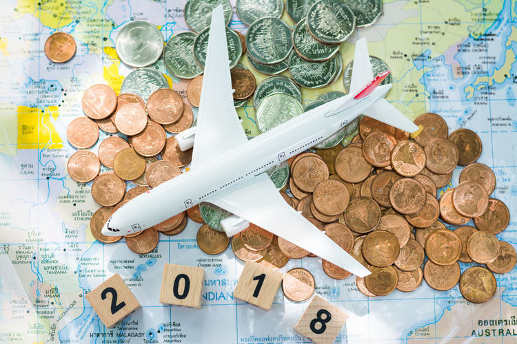 Close-up high angle view of coins and model airplane on map