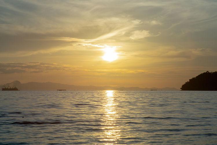 Landscape of sea with silhouette of island and orange light of sunrise