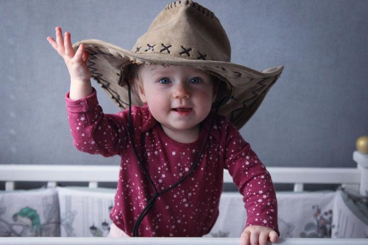 Portrait of cute girl smiling in cowboy hat