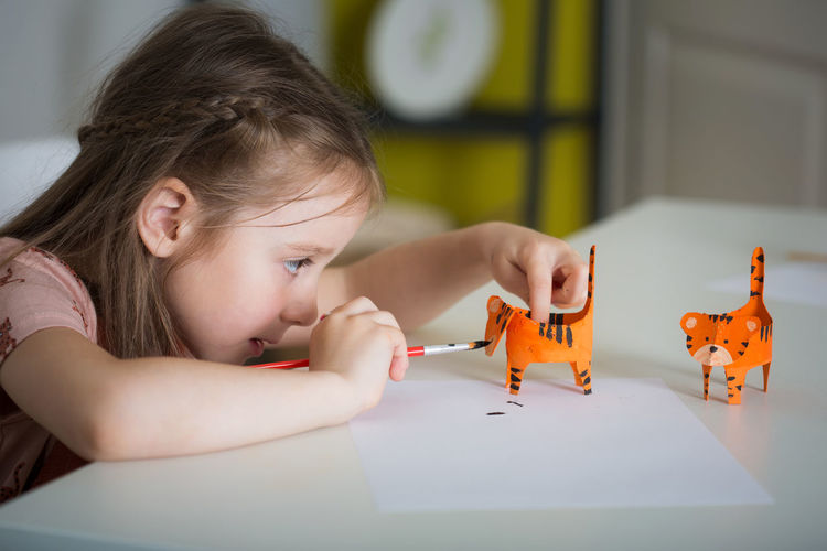 Portrait of girl with toys on table