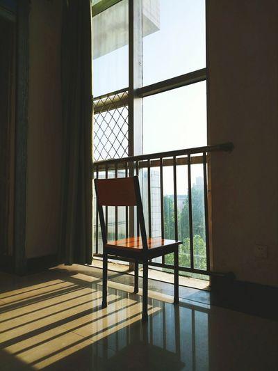 Chair in empty room by window