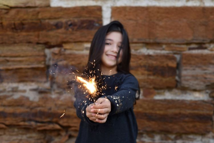 Portrait of girl holding lit sparkler against wall