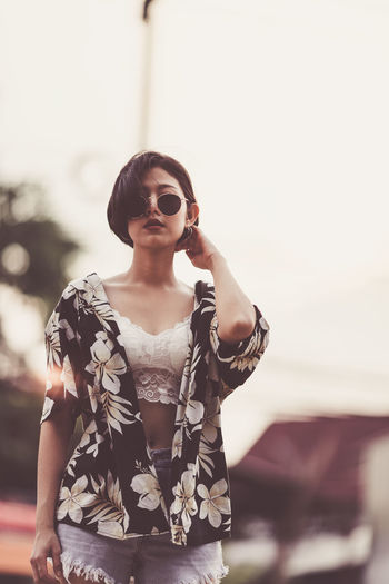 Portrait of sensuous young woman wearing sunglasses while standing against sky