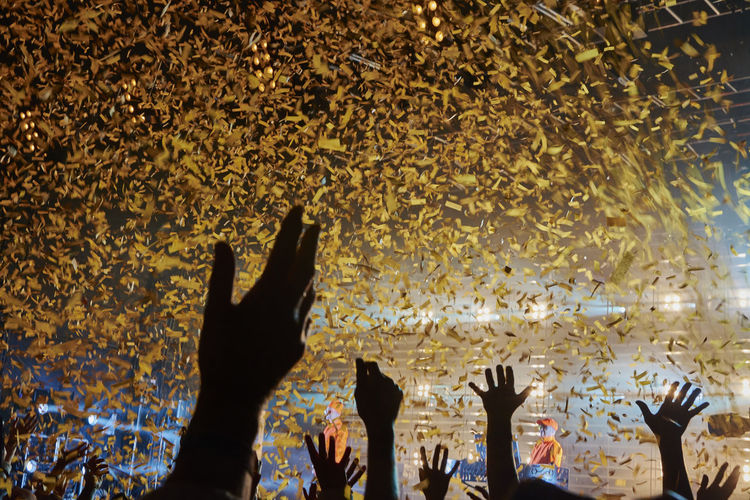 Cropped Arms Raised Below Confetti During Music Festival
