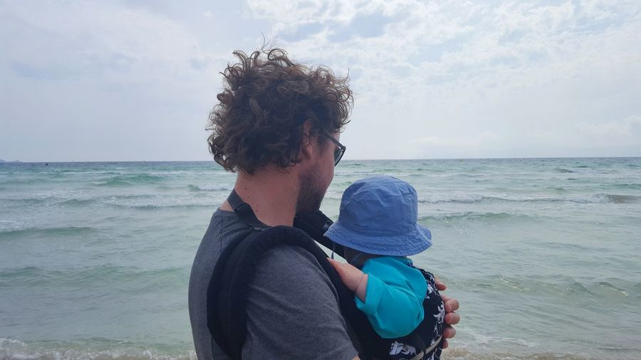 Side view of man and son at beach against sky