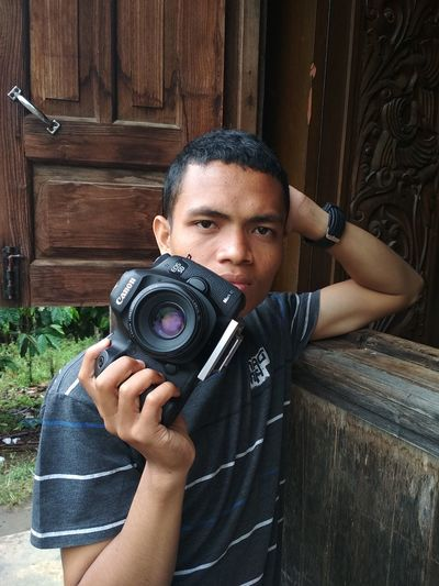 Portrait of young man photographing