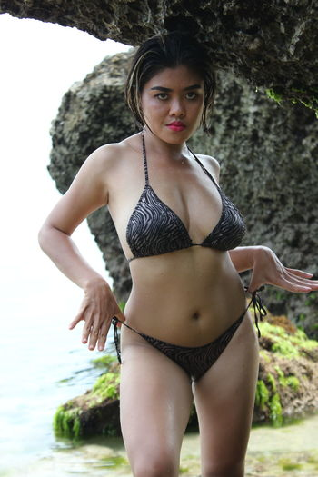 Portrait of woman in bikini standing against rock formation