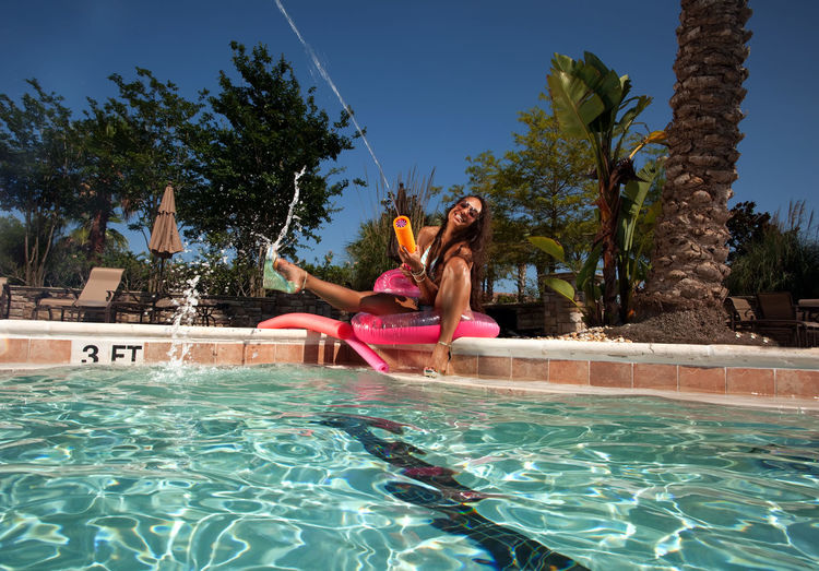 Portrait Of Happy Bikini Woman With Squirt Gun While Sitting On Inflatable Ring By Pool