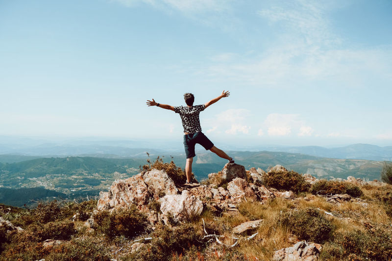 Man with arms raised on rock against sky