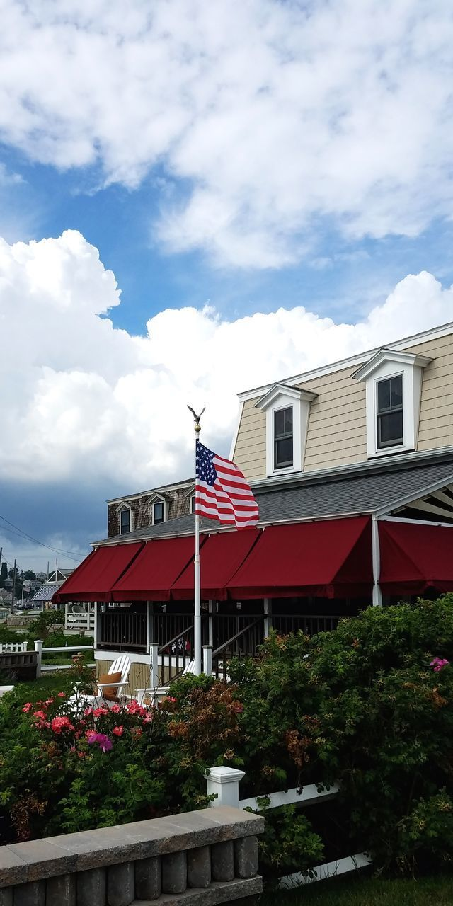 architecture, building exterior, built structure, cloud - sky, sky, building, plant, nature, house, patriotism, day, no people, residential district, flag, outdoors, city, red, tree, window