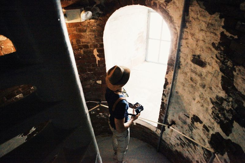 Man in hat standing in front of arch window