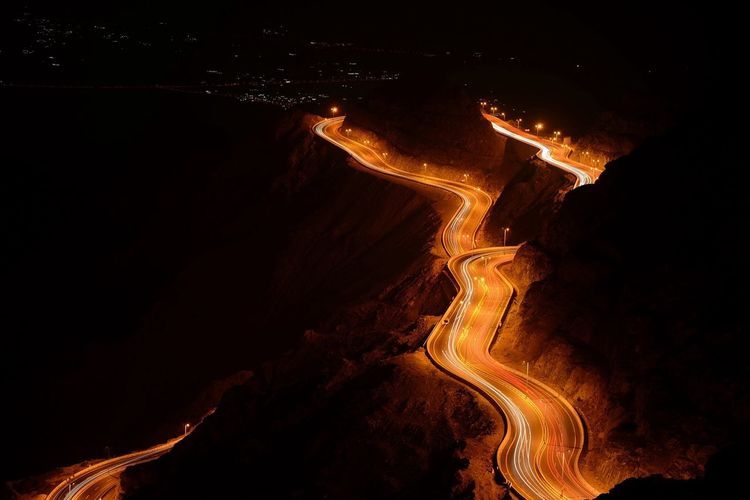 High angle view of light trails on country road at night