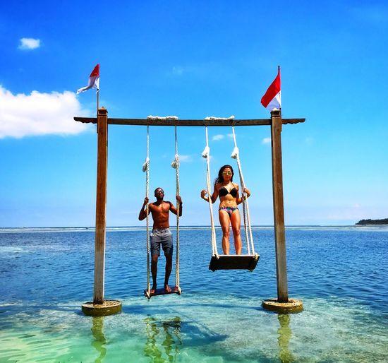 Friends on swing in sea against sky